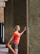 Woman stretching against a pillar