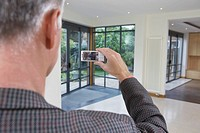 Real estate agent photographing new property (thumbnail)