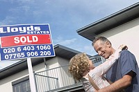 Couple embracing outside new home with sold sign
