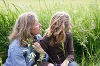 Mother and daughter sitting together in tall grass wind blowing their hair Canada