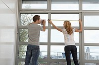 Couple measuring apartment window