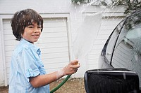 Boy 7_9 washing car with hose