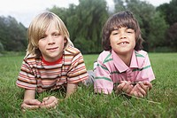 Portrait of two boys 7_9 lying in meadow