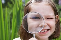 Portrait of girl 7_9 looking through magnifying glass