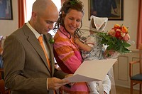 bridal couple with certificate of marriage