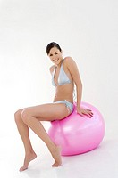 Young smiling woman, sitting on big pink balloon