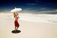 Young woman in bikini and pareo with parasol on the beach (thumbnail)