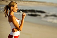 Young woman standing on beach, drinking water from a bottle