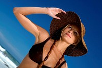 Young woman in bikini on the beach, hat and necklace