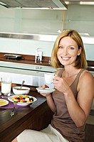 Smiling woman having breakfast