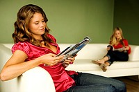 2 women reading on sofa