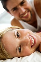 Young smiling couple in bed (thumbnail)