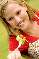 Portrait of a young smiling woman eating salad, outdoors