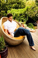 Young man sitting in armchair reading a book, outdoors