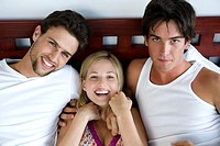 2 men and a woman lying in bed, smiling for the camera