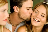 Young woman looking at man kissing smiling woman