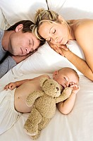 Young couple and baby sleeping, indoors