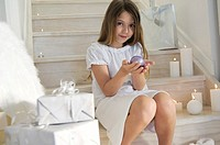 Little girl sitting indoors, holding a Christmas ball, indoors