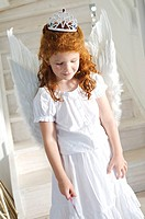 Little girl in an angel costume, indoors