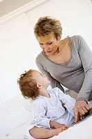 Senior woman with little girl on bed (thumbnail)
