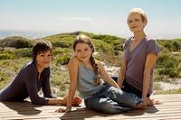 Female members of three generation family looking at camera, outdoors