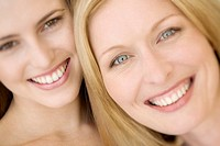 Portrait of two women smiling for the camera, indoors