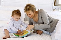 Senior woman reading with little girl, on bed