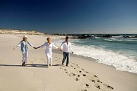 Couple and senior woman holding hands on beach