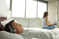 Couple in bedroom, man listening to music, woman using laptop, indoors