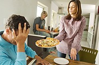 Parents and teenager in living room, woman holding a pizza, indoors