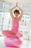 Young woman in yoga attitude, indoors (thumbnail)