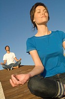 Young couple in yoga attitude, outdoors