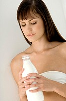 Portrait of a young woman holding bottle of milk