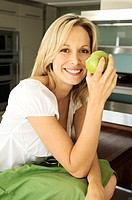 Young smiling woman eating an apple (thumbnail)