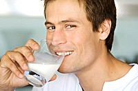 Portrait of a young man drnking glass of milk