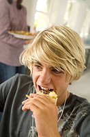 Portrait of a teen boy eating, woman in background