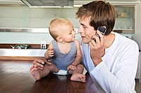 Young man phoning, embracing baby