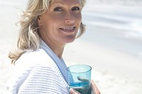 Portrait of smiling woman on the beach, holding glass of water