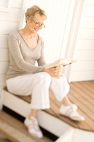 Smiling senior woman reading a book, sitting on wooden terrace