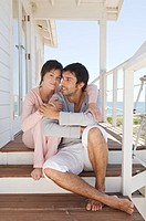 Couple embracing, sitting on wooden terrace