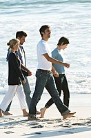 2 couples holding hands, walking on the beach