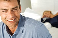 Portrait of smiling man, woman lying on bed in background