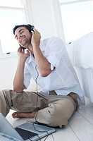 Young man listening to music with laptop