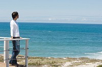 Young man leaning against balustrade, looking out to sea