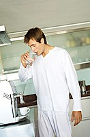 Young man drinking water in kitchen