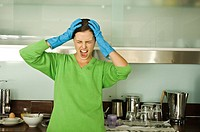 Young woman screaming in kitchen, hands on head