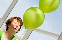 Portrait of young smiling woman holding green balloons