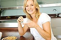 Young smiling woman holding coffee cup