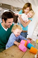 Couple and 2 children playing in kitchen (thumbnail)