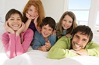 Smiling couple with 3 children lying on bed